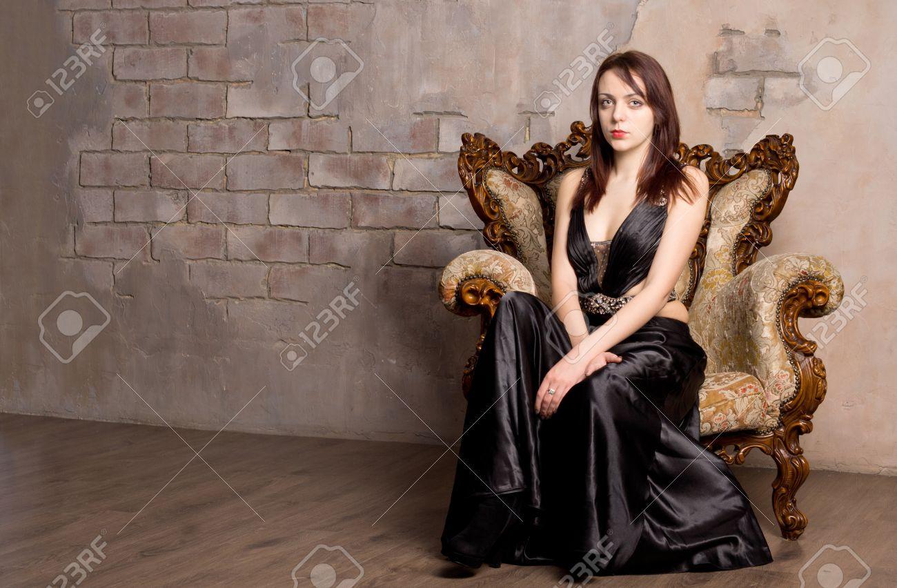 glamorous frau in einem abendkleid posiert für ihre poirtrait auf einem  vintage-holz-sessel sitzend gegen eine alte steinerne innenwand