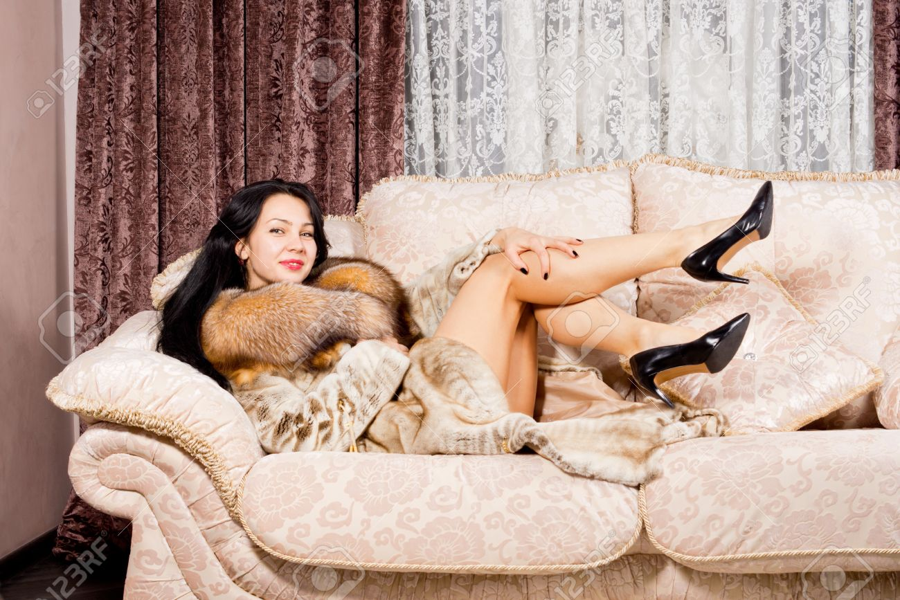 sexy woman in fur coat and high heels reclining on a couch with