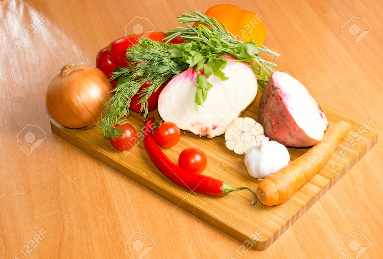 Selection of farm fresh vegetables and sprigs of herbs on a chopping board in the kitchen ready to be turned into a delicious meal on a wooden table top Stock Photo - 18572658