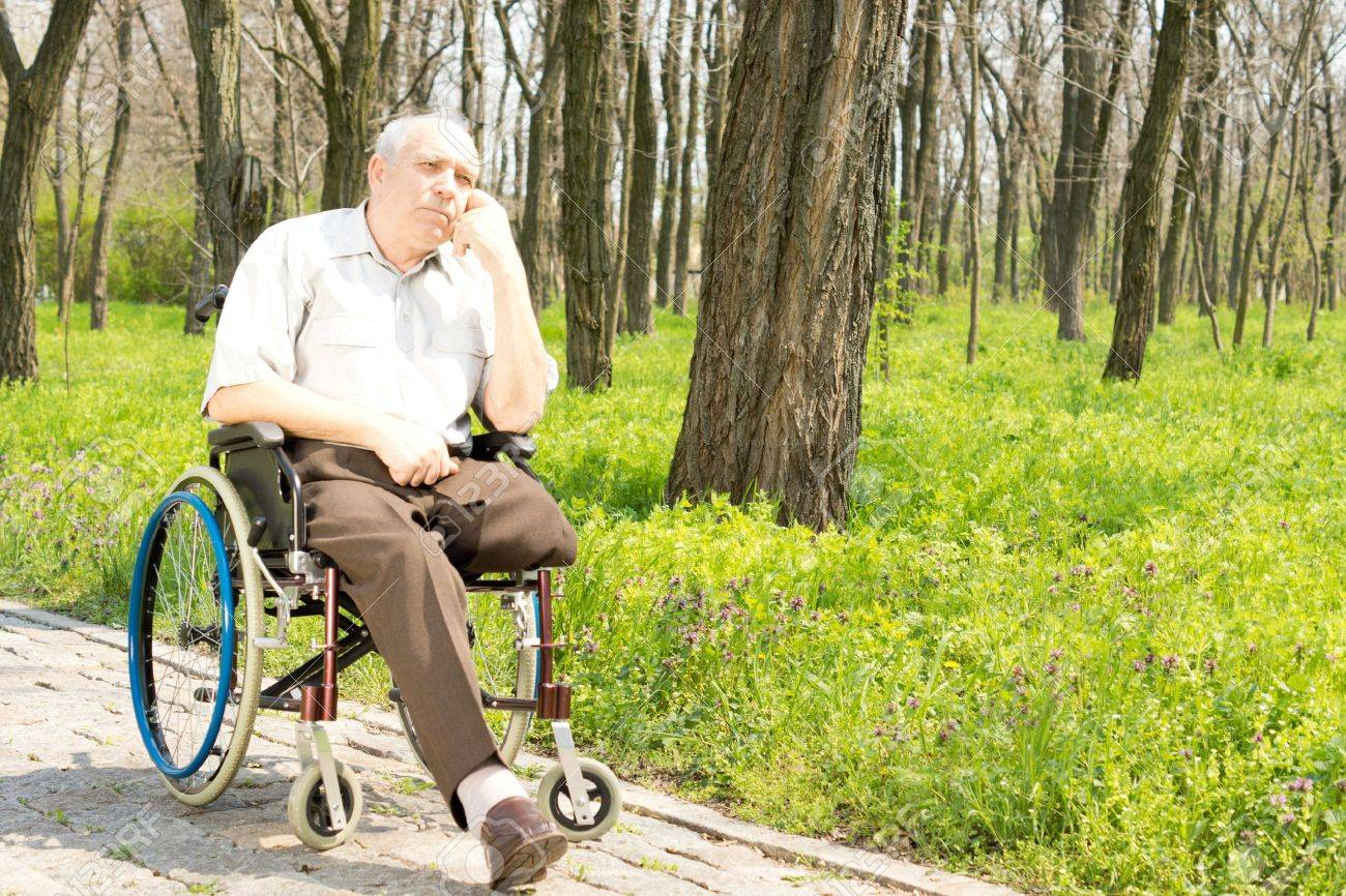 Pensive elderly amputee sitting alone on a rural pathway in his wheelchair with his chin resting on his hand staring into the distance - 19638462
