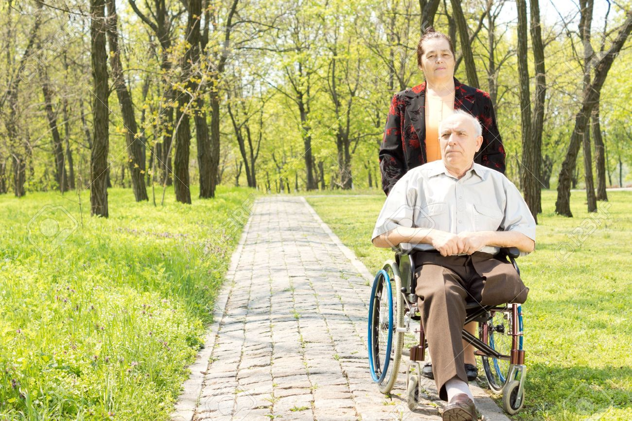 Wife walking a disabled man in a wheelchair who has had one leg amputated through a peaceful rural wooded park - 19662681