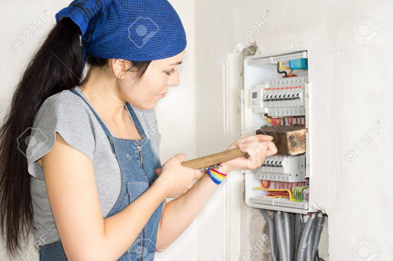 housewife armed with a wooden mallet attacking an open electrical fuse box  in frustration as she