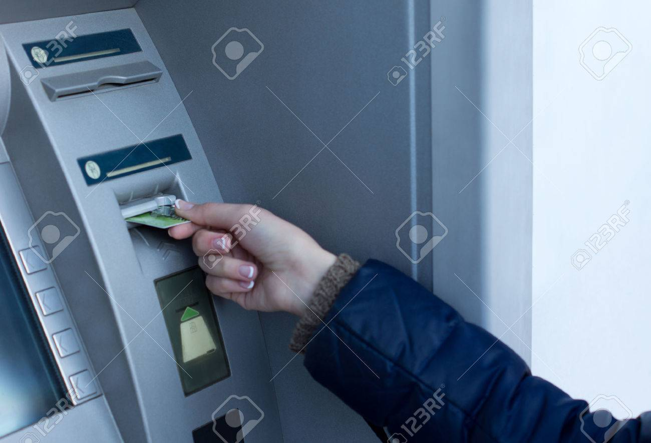 Woman inserting her bank card at the ATM outside a bank so that she can withdraw cash by entering her pin code - 24615385