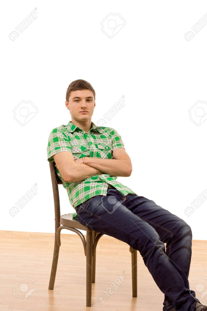 Confident young man sitting comfortably in an old wooden chair reclining backwards with his legs extended  sc 1 st  123RF Stock Photos & Confident Young Man Sitting Comfortably In An Old Wooden Chair ... islam-shia.org