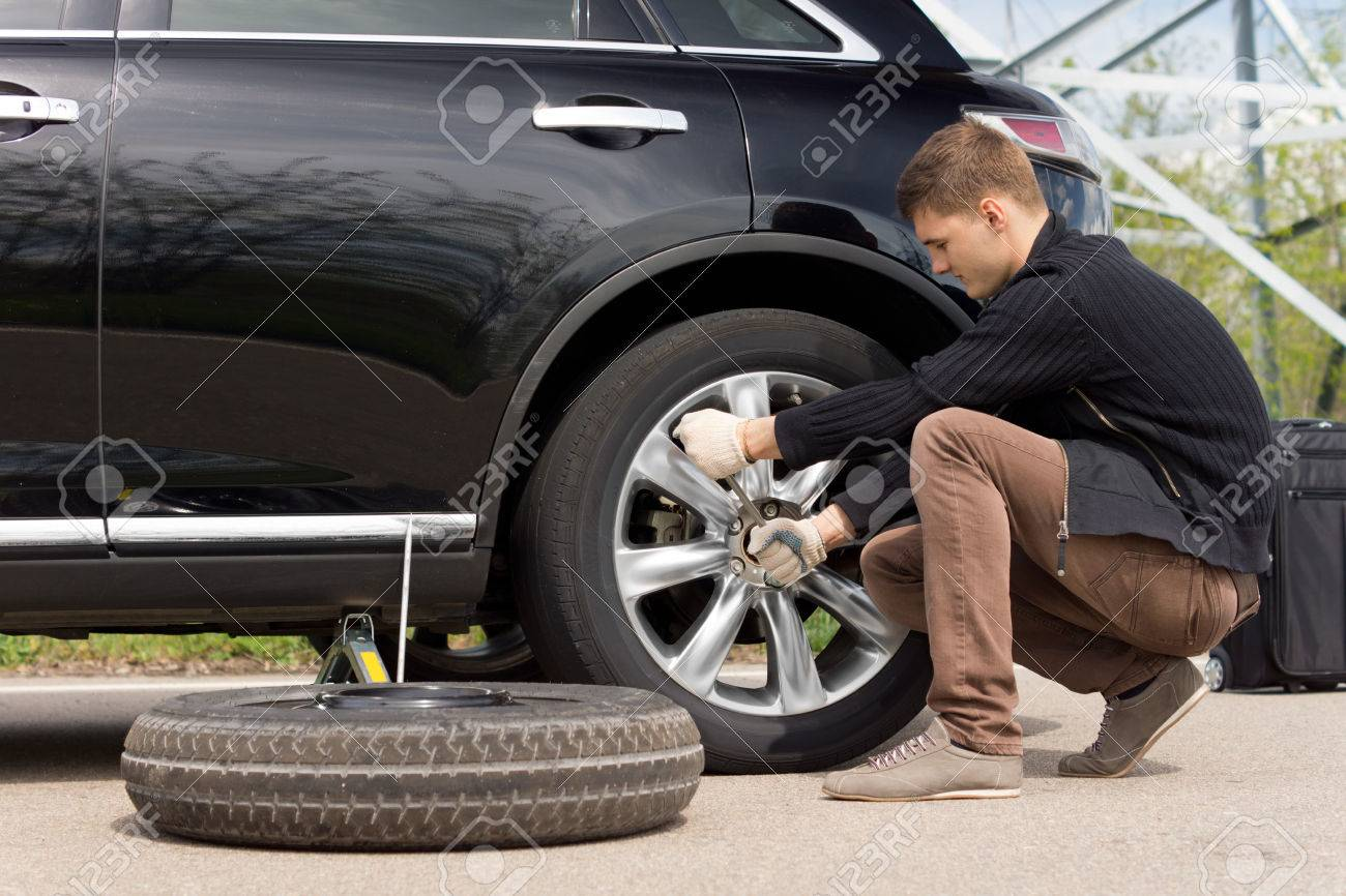 Young man changing the punctured tyre on his car loosening the nuts with a wheel spanner before jacking up the vehicle - 28229333
