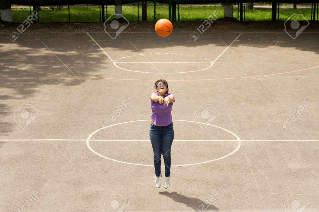 Stock Photo - Young girl shooting a basketball at the hoop and net as she  practices on an outdoor basketball court jumping into the air as she  launches the ... 917a403c3b6