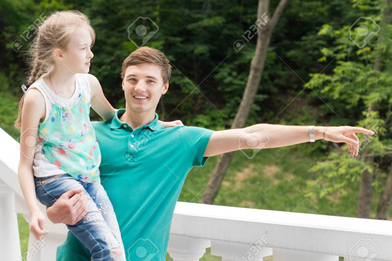 Young man carrying his small sister on his arm and pointing to