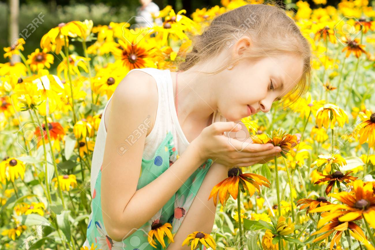 Cute Little Girl Playing With Bright Yellow Flowers Cupping One