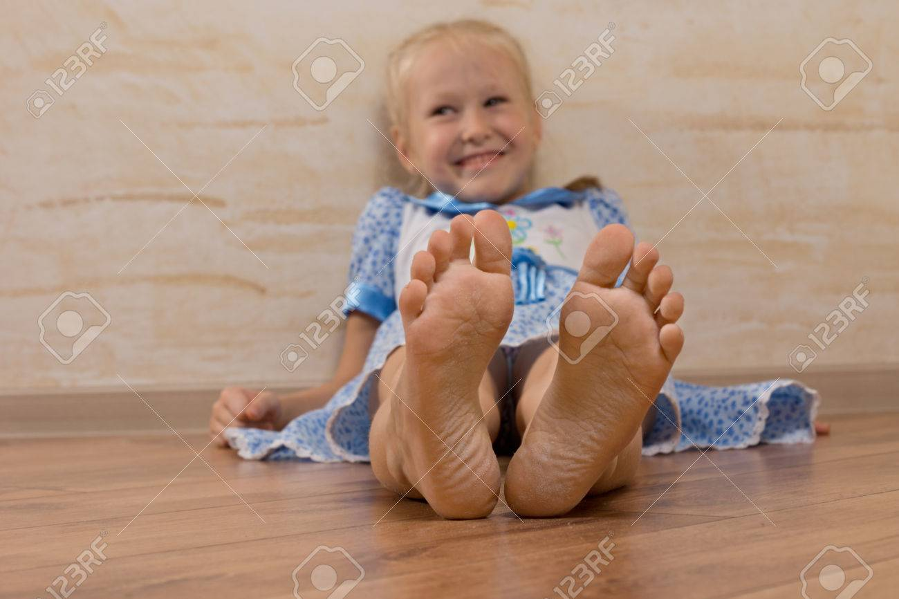 smiling young girl showing feet on camera isolated on wooden