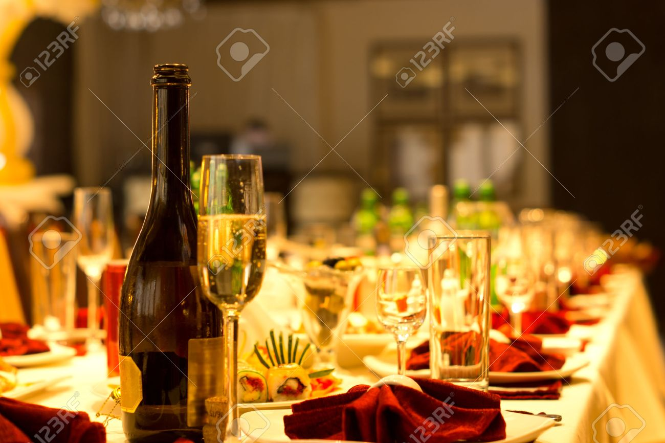 Champagne in a bottle and elegant tall flute on a formal dinner table set with luxury linen and glassware with red accents for a celebration and party - 30680139