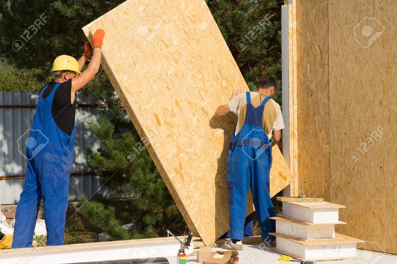 Construction workers positioning timber wall panels in a new build prefabricated wooden house - 32955393