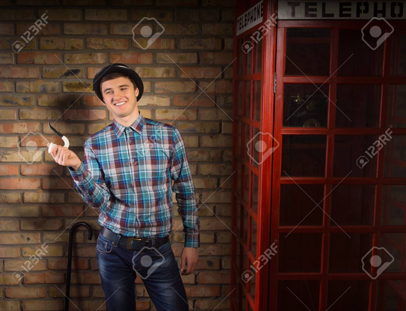 8eb06c5a10 Happy Young Handsome Man in Checkered Shirt and Jeans with Trendy Hat  Holding Smoking Pipe Near