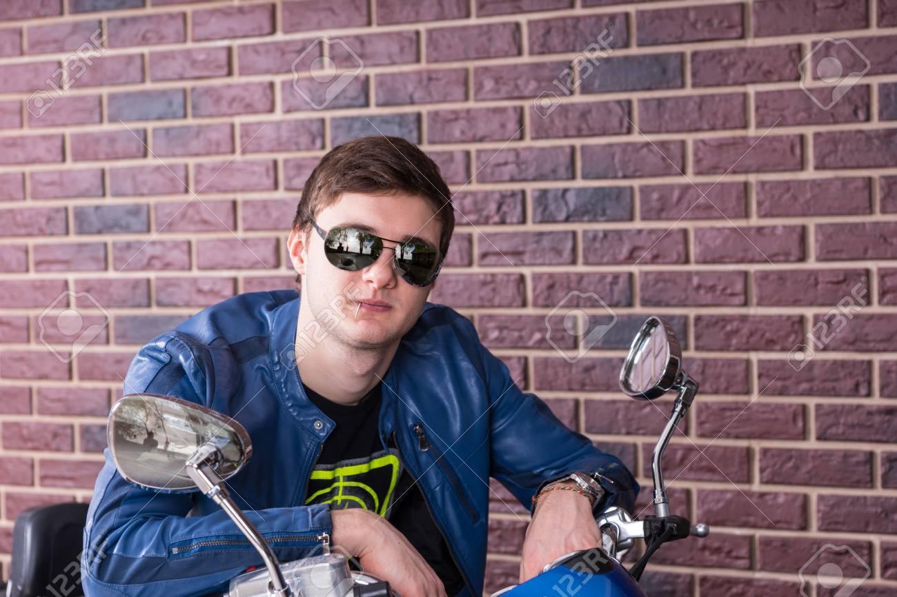 454c48cbac Foto de archivo - Moda joven en una moto inclinada sobre el manillar en sus  gafas de sol de moda para sonreír a la cámara