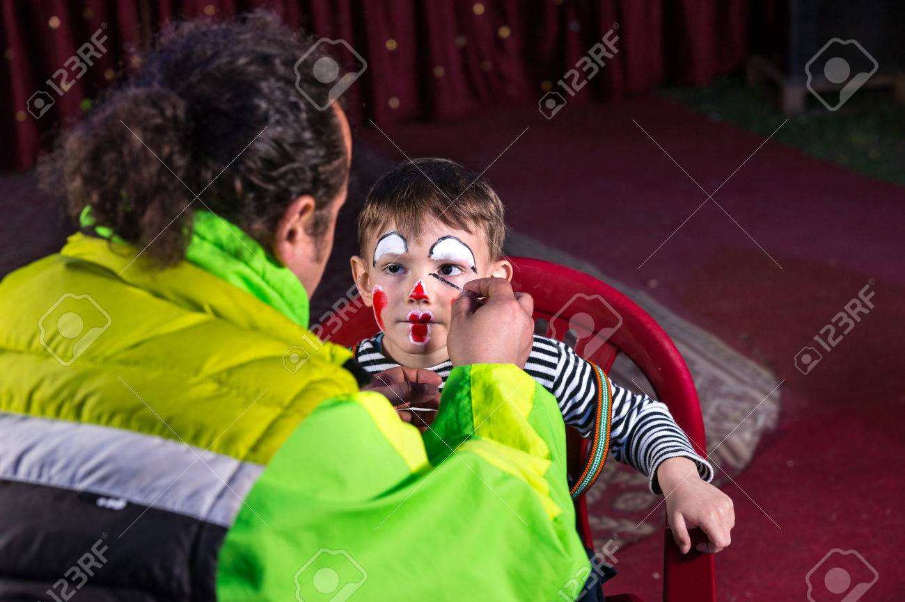 Looking Over Shoulder Of Man Applying Clown Make Up To Face Of Young Boy  Sitting In