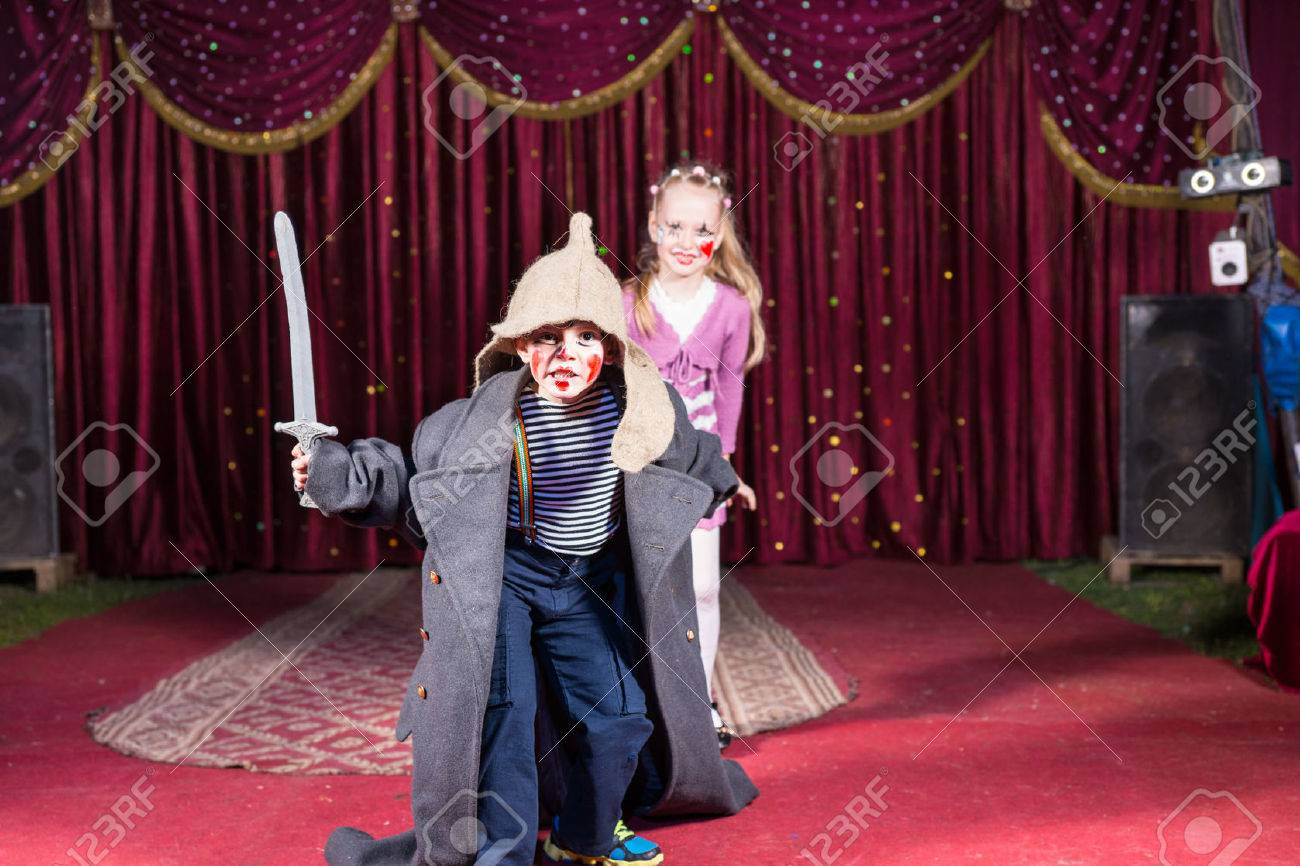Cute talented boy playing the role of a brave Russian warrior fighting with a sward to defense his beautiful wife, in a theatrical performance at school - 39808001