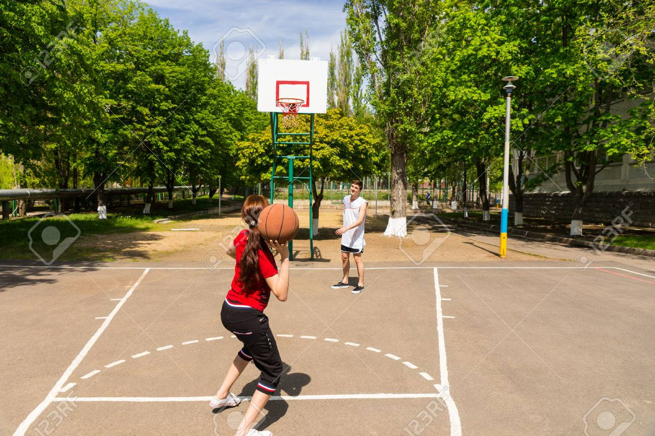Young Athletic Couple Playing Basketball Together Man Watching