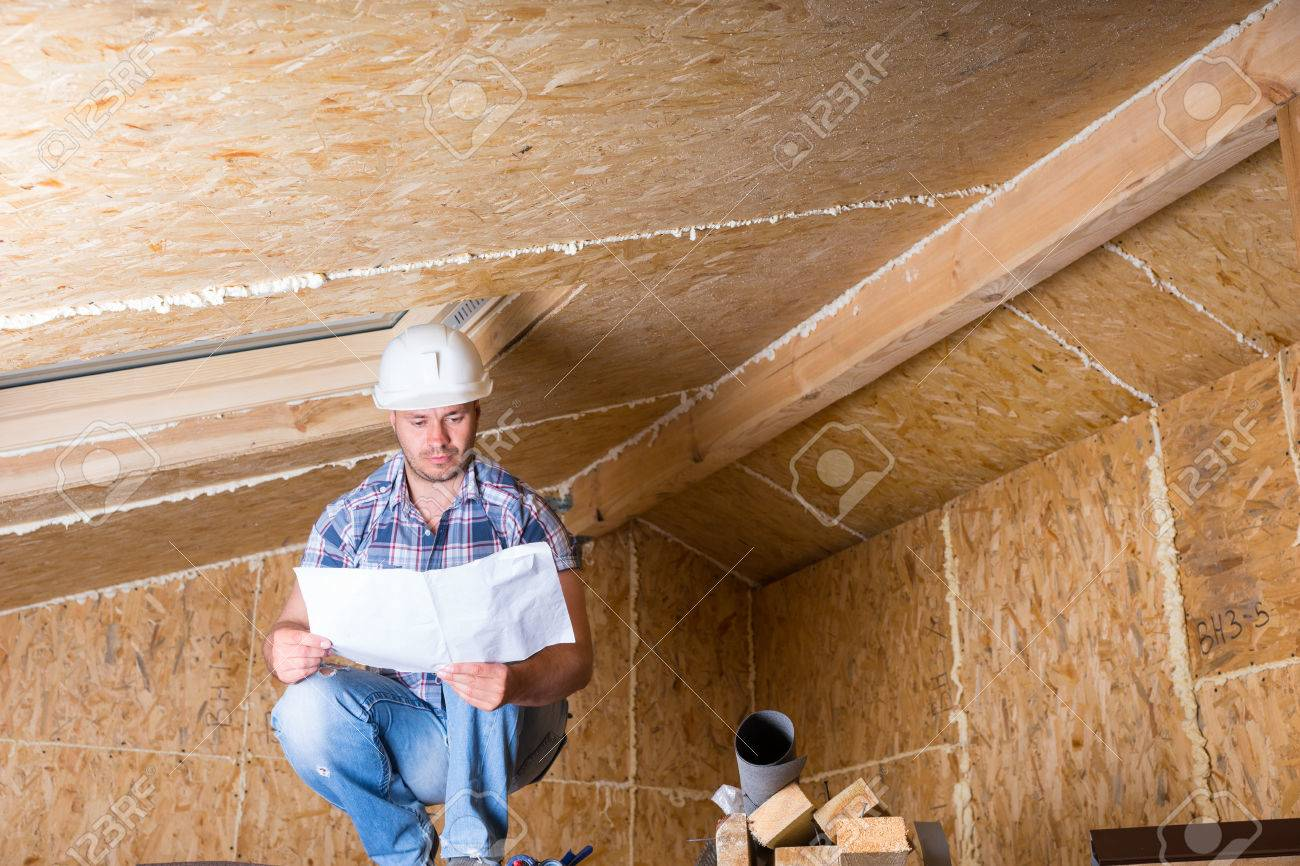 Male Construction Worker Builder Wearing White Hard Hat Crouching on Elevated Scaffolding and Reading Plans near Ceiling of Unfinished Home with Exposed Plywood Particle Board - 41018622