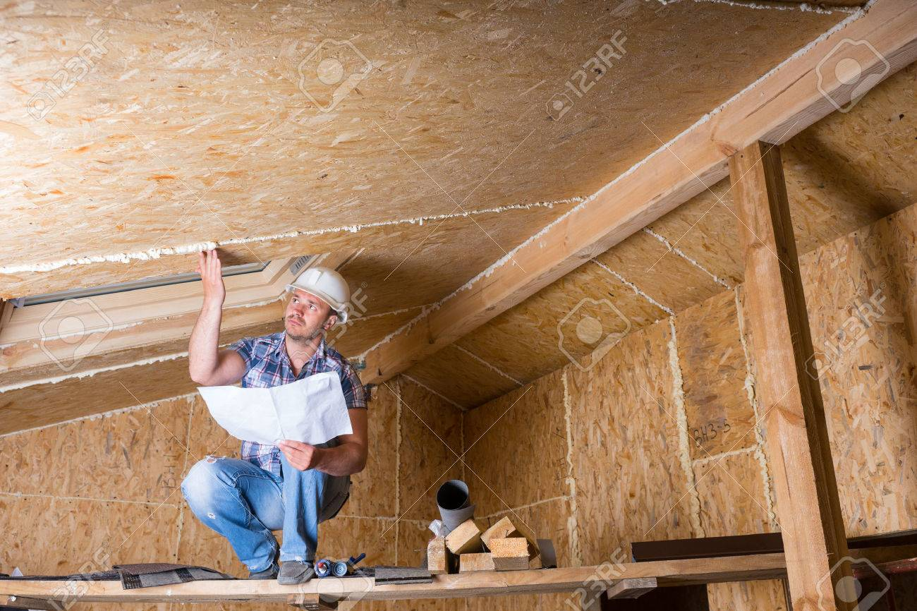 Male Construction Worker Builder Wearing White Hard Hat Crouching