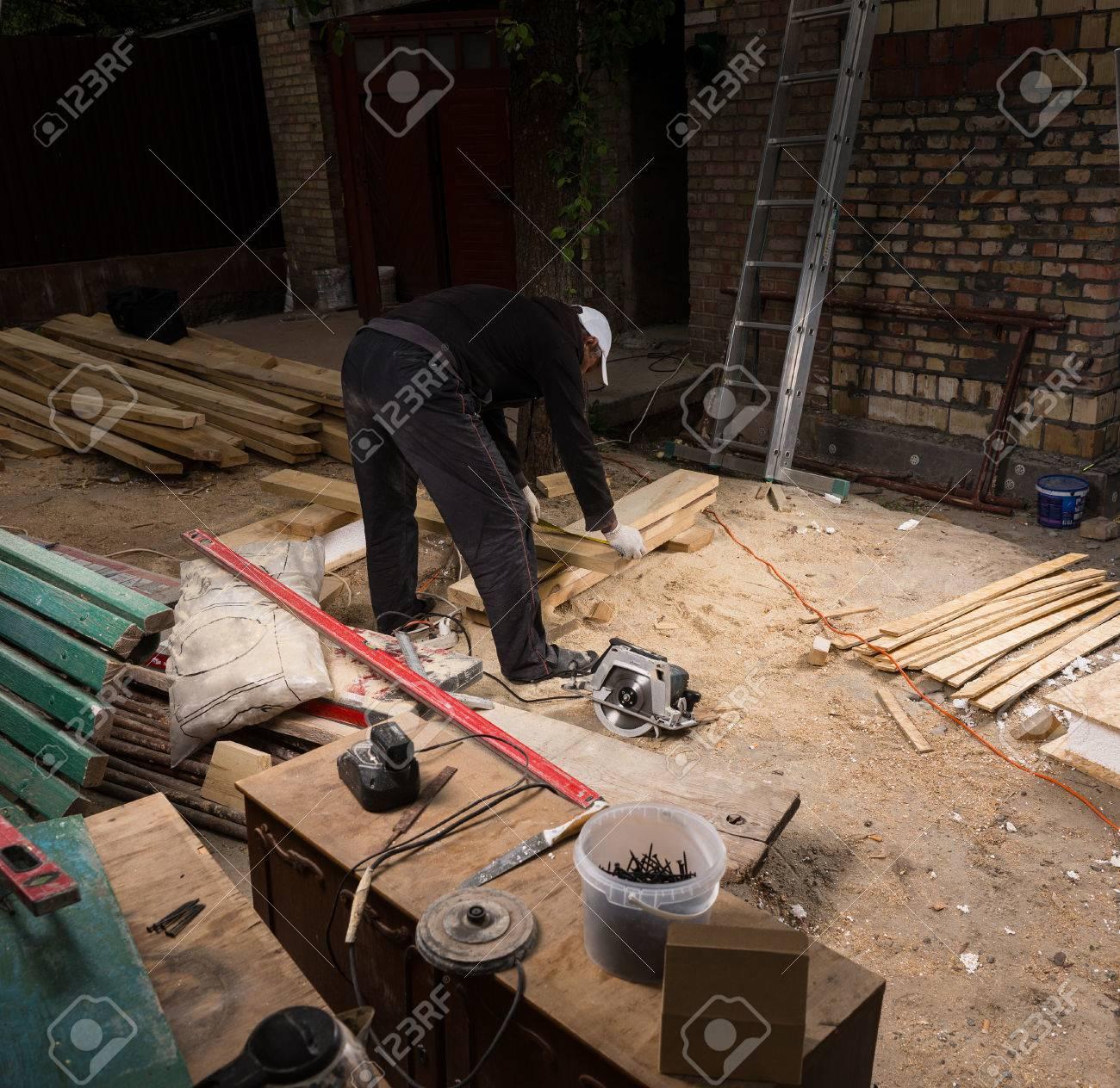 Vue En Plongee De L Homme Utilisant Hand Held Scie Pour Couper Des