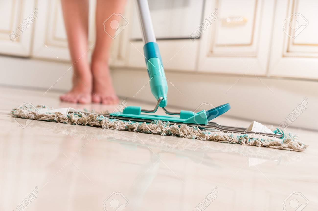 Low Angle View of Young Woman Mopping Kitchen Floor with Focus on Shiny Clean Floor and Mop - 45231952
