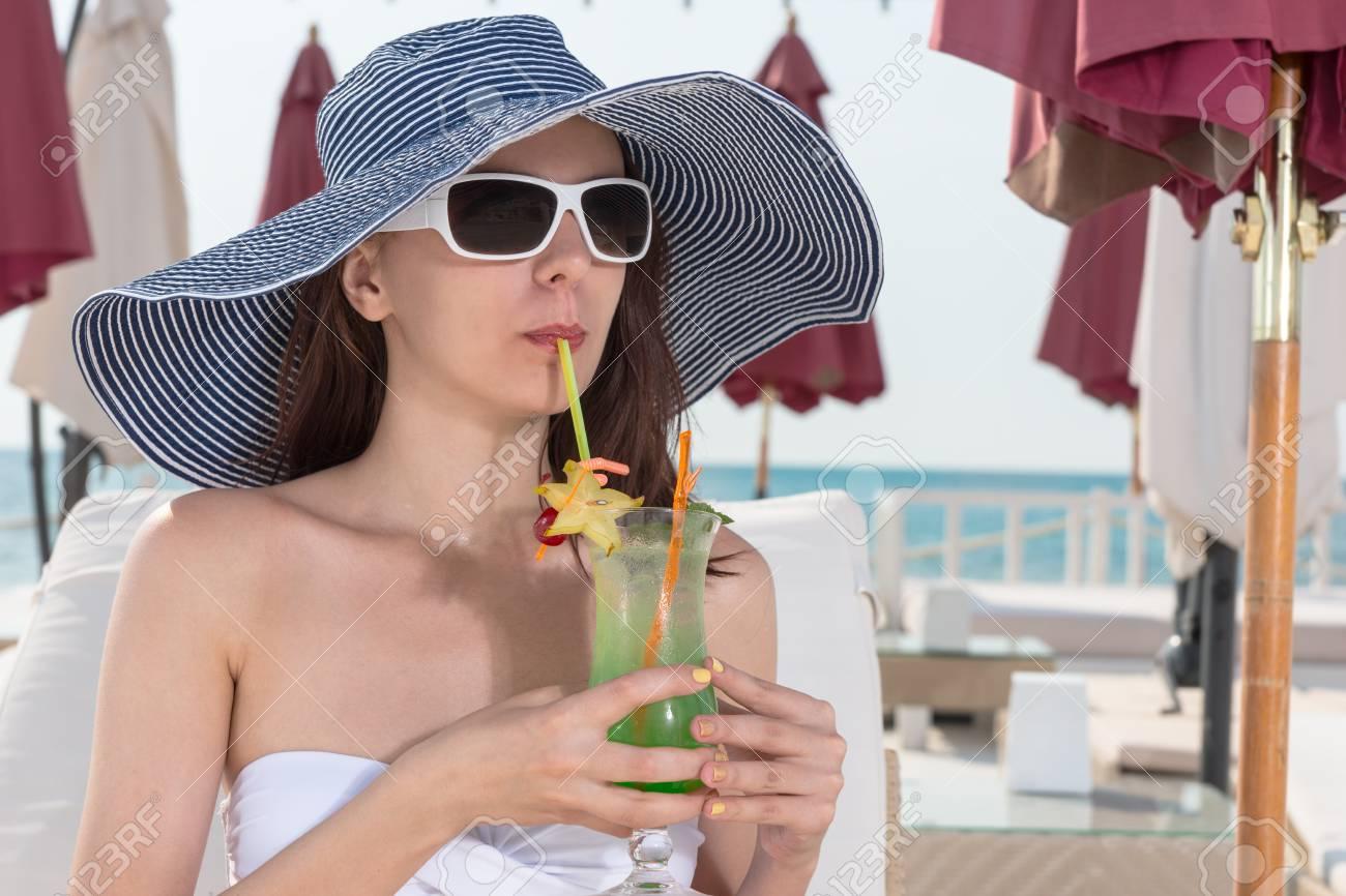 Au Bord Elégante Elle Des Larges Fruits Chapeau Cocktail Se De Détend Mer Femme Sirotant Glacée Dans Un Lunettes Soleil Comme À Jeune Une Et vwmnyON80