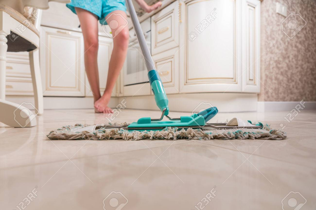 low angle view of young woman mopping kitchen floor with focus