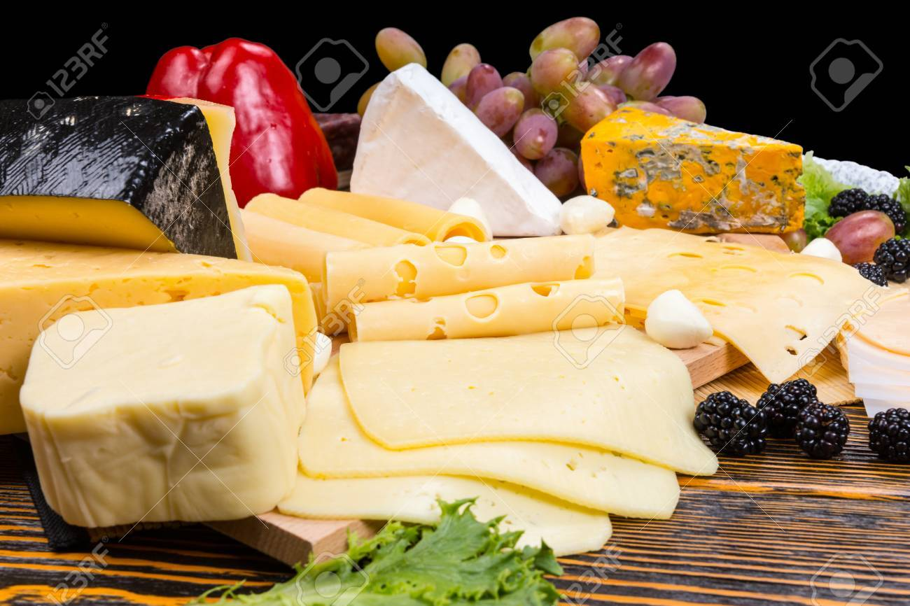 Gourmet selection of cheeses on a cheeseboard garnished with fresh blackberries, olives, grapes, and red bell pepper - 45235311