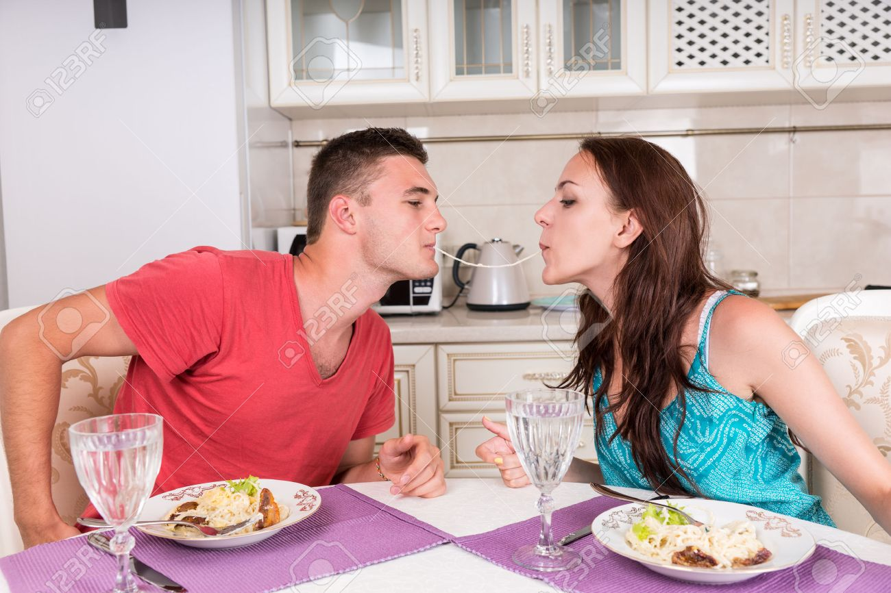 Young Couple Having Romantic Dinner Together at Home - Man and Woman Sharing Single Spaghetti Noodle Getting Closer to Kissing - 45318972