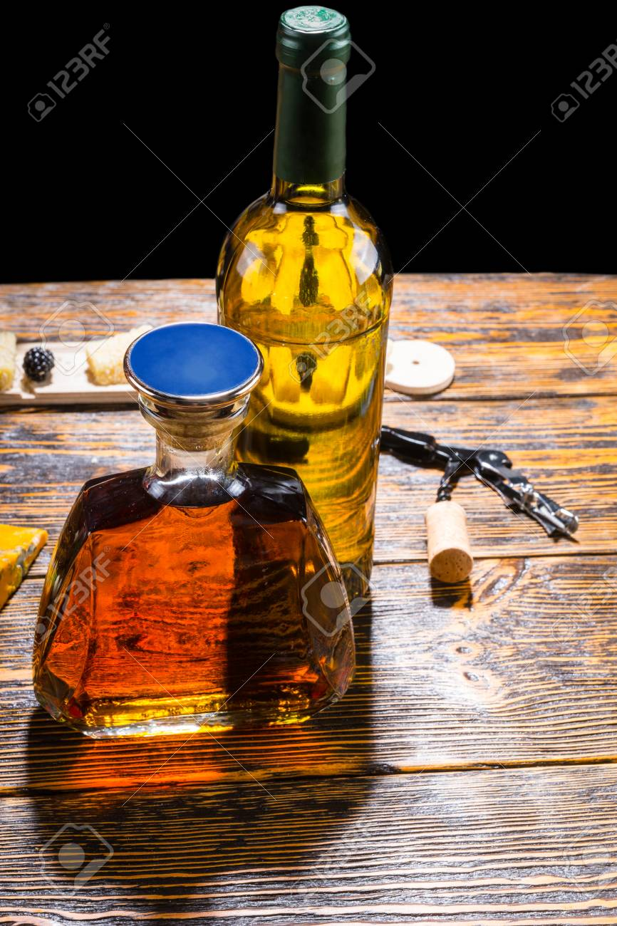 Stylish Whiskey Decanter And Bottle Of Wine Standing On A Wooden
