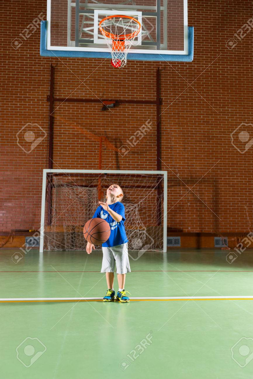 Young Boy Practicing His Shooting At Goal On An Indoor Basketball ...