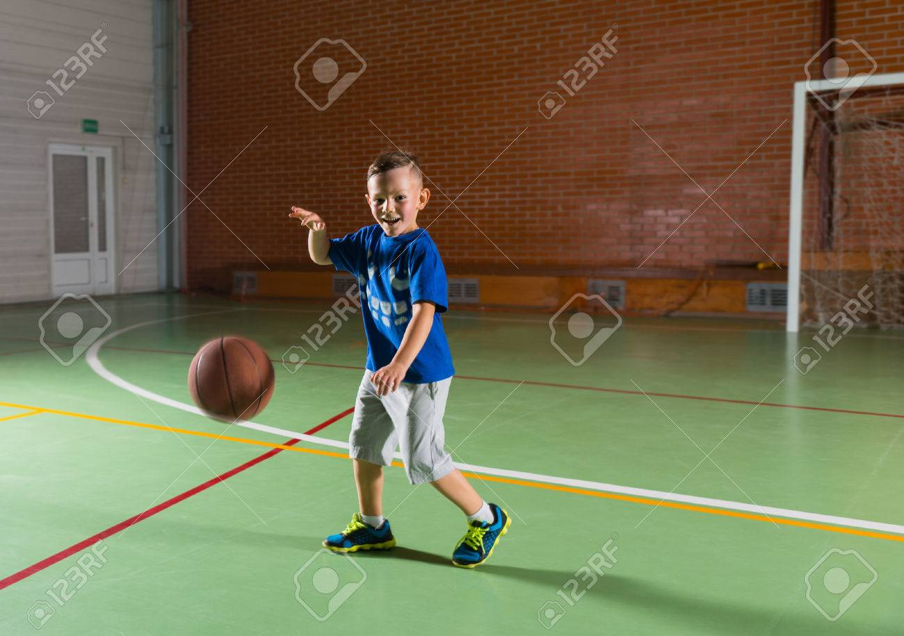 Laughing young boy playing basketball on an indoor court as he runs along bouncing the ball and grinning at the camera - 50842312