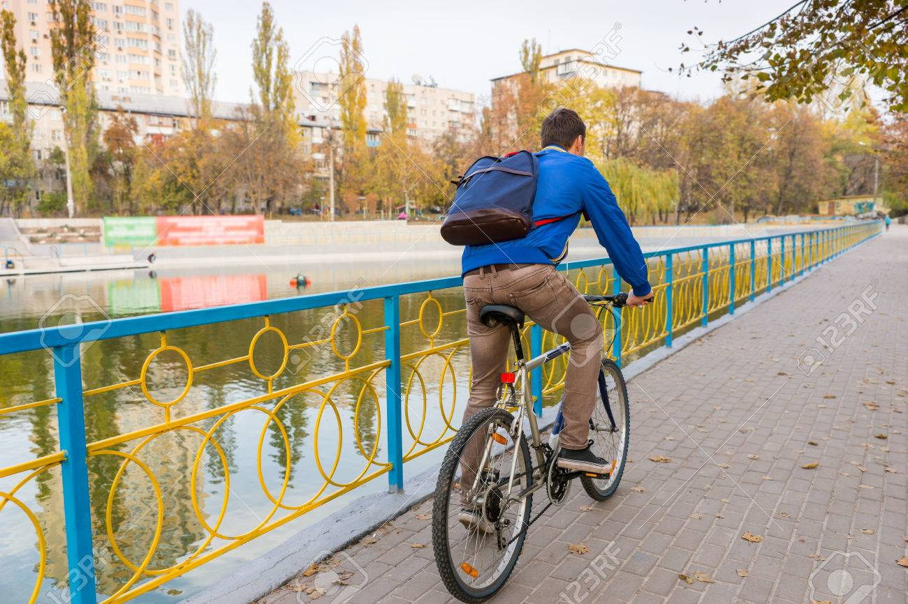Full Length Rear View of Young Man Wearing Backpack and Riding Bicycle on Waterfront Promenade Through Urban Park in Autumn - 50666244