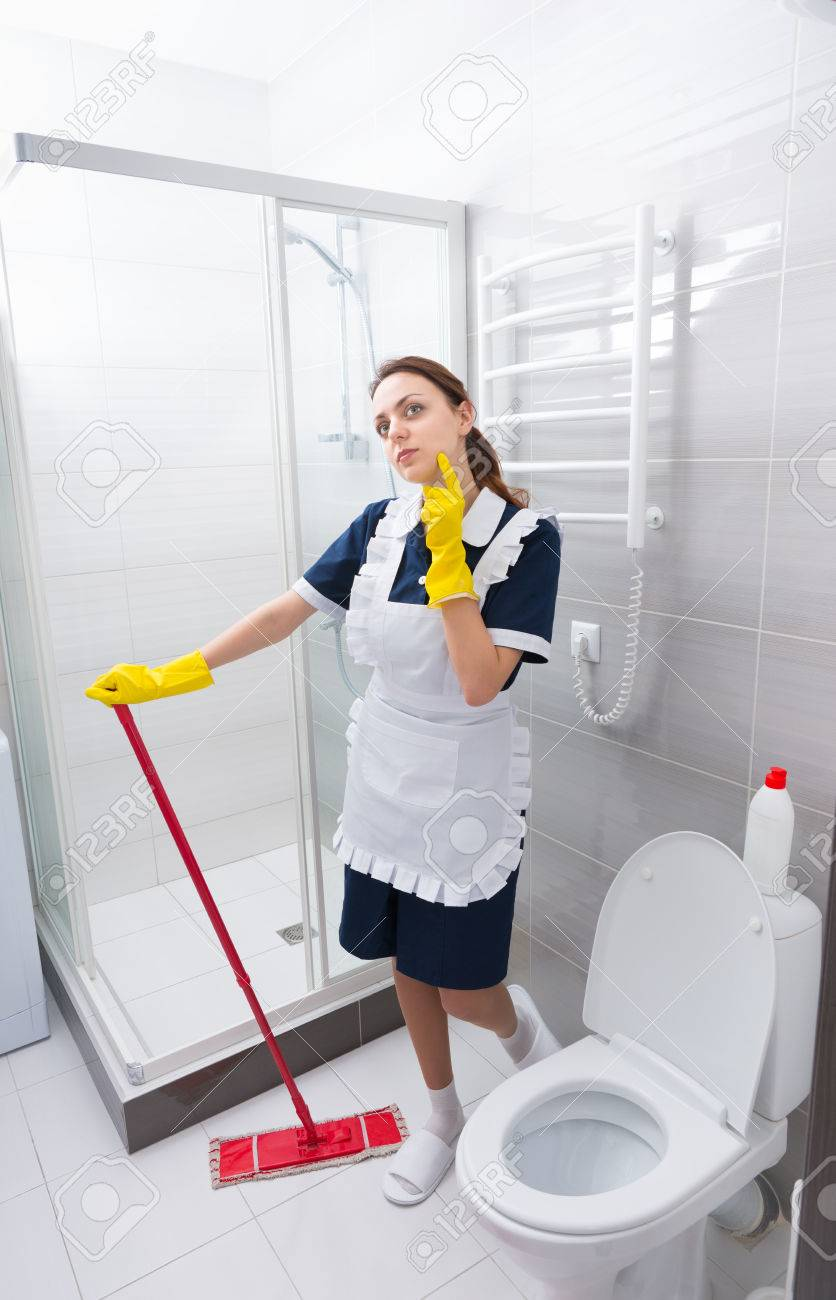 Pretty Young Housekeeper Or Maid Relaxing On The Job Standing - Bathroom maid