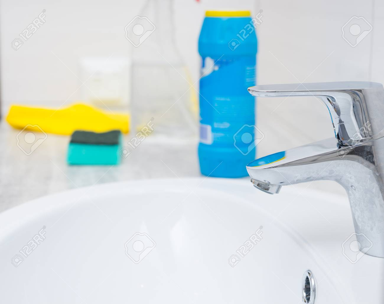 Close Up Of Chrome Sink Spigot And Cleaning Chemicals Bottle