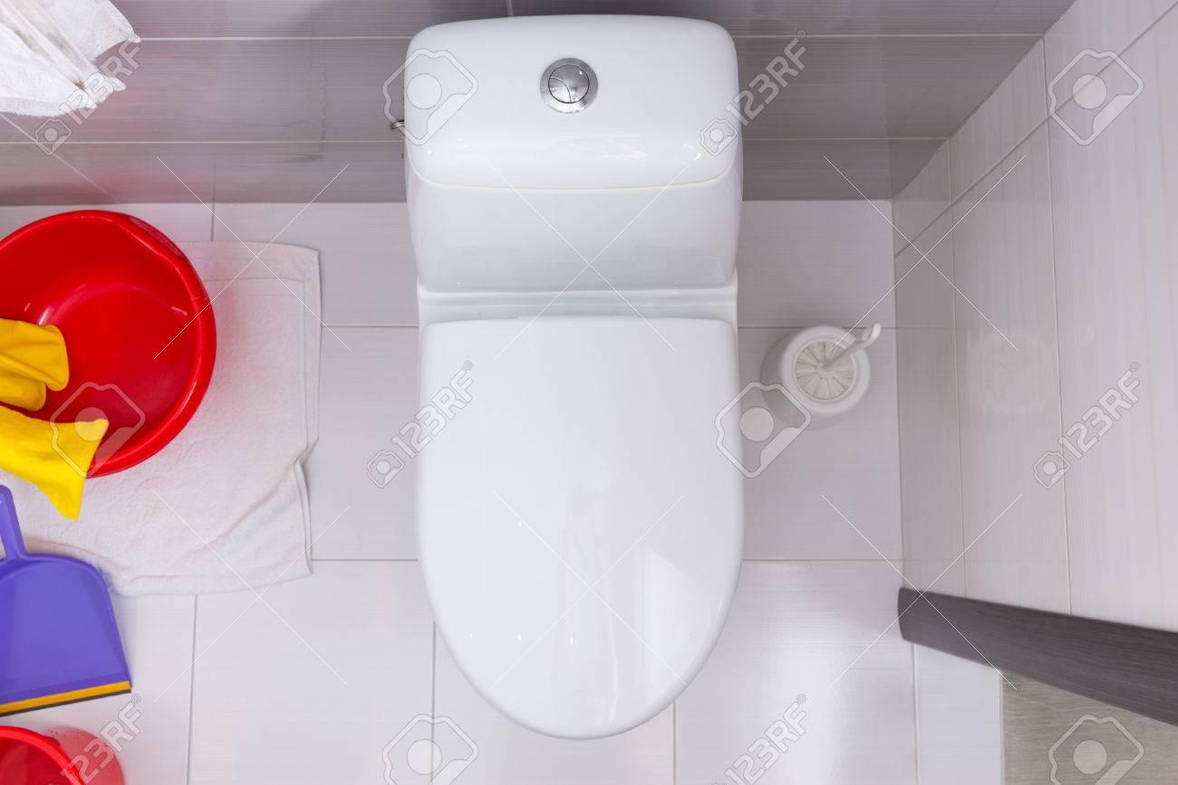Toilette Blanc Et Gris vue aérienne d'une toilette fermé dans une salle de bain carrelée blanc et  gris avec un assortiment coloré d'un seau en plastique, baignoire, poêle et