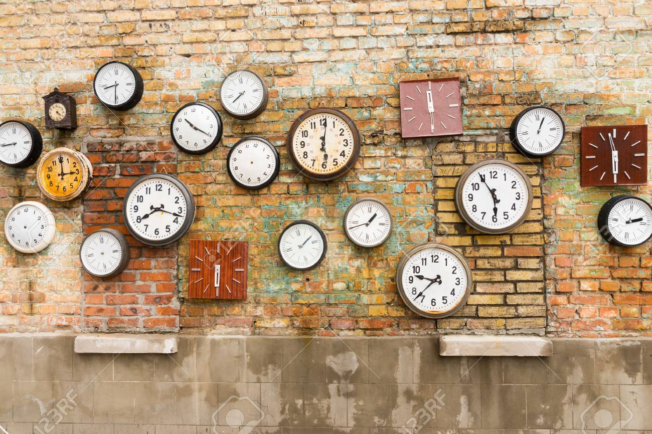 Abstract background composed of numerous round and square clocks on a brick wall - 57717466