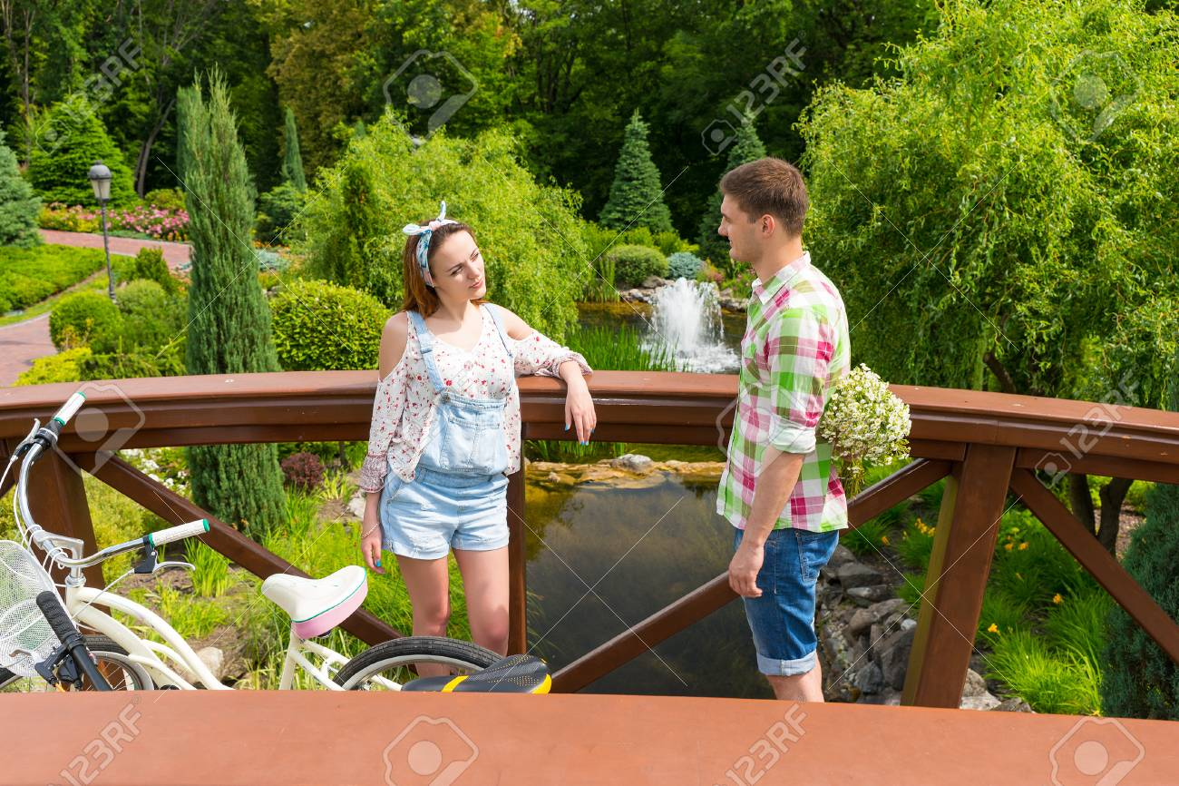Young female and male holding large bouquet of little white flowers stock photo young female and male holding large bouquet of little white flowers behind the back standing on a footbridge near bicycles and smiling outside izmirmasajfo