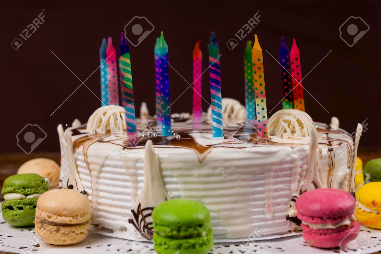 White Birthday Cake With Lots Of Colored Candles Near Different