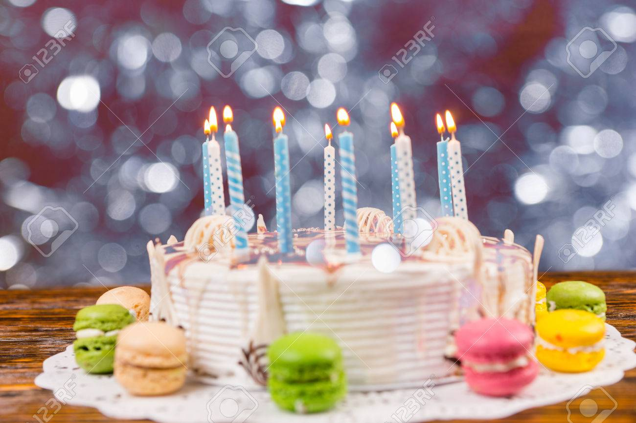 White Birthday Cake With Lots Of Burning Candles Near Different