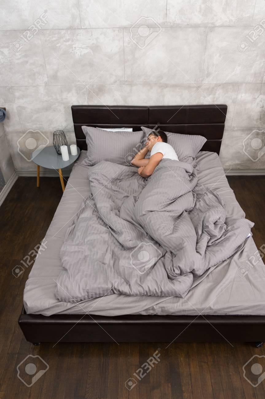 Lit Pour Jeune Homme jeune homme dormant seul dans un lit élégant avec des couleurs grises et  une table de chevet avec des bougies dans une chambre de style loft