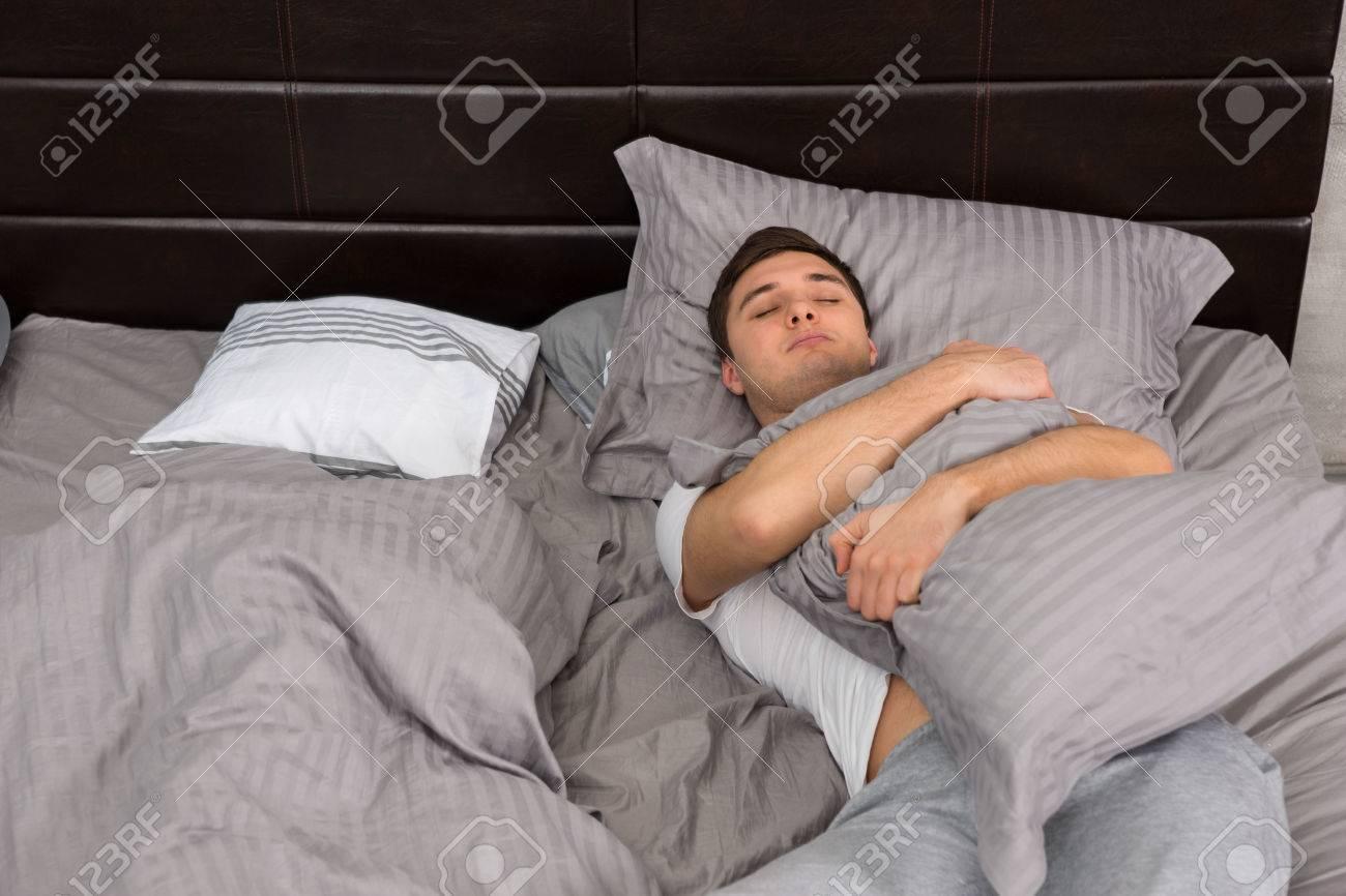 le pyjama couverture dans lit près étreignant un homme dans table de seulsans oreiller et fatigué de chevet Jeune des et tons gris dormir élégant f6bgy7