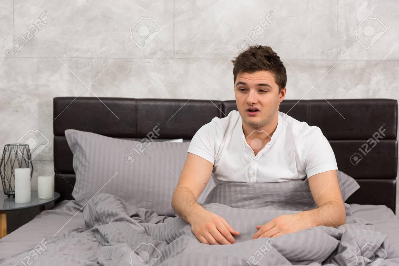 Candele Camera Da Letto : Il giovane si svegliò e seduto a letto elegante nei colori grigio