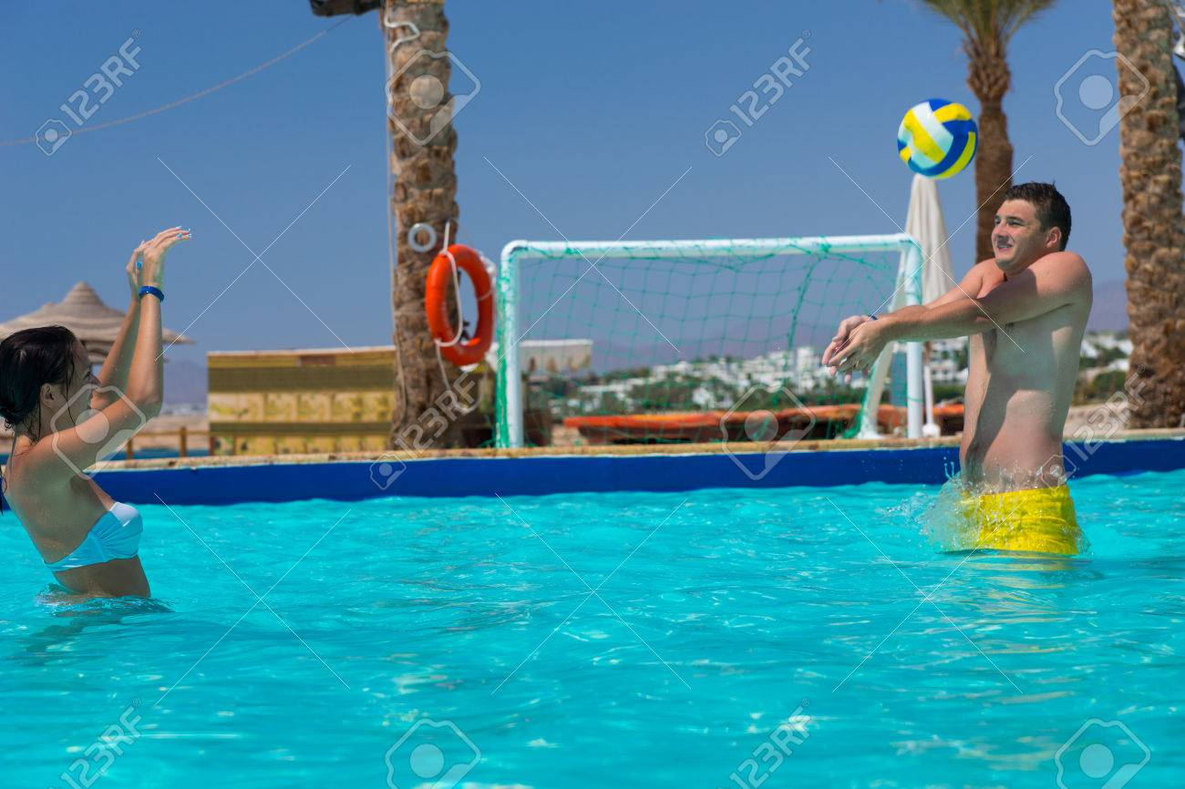 Young couple playing volleyball in the swimming pool at the hotel..