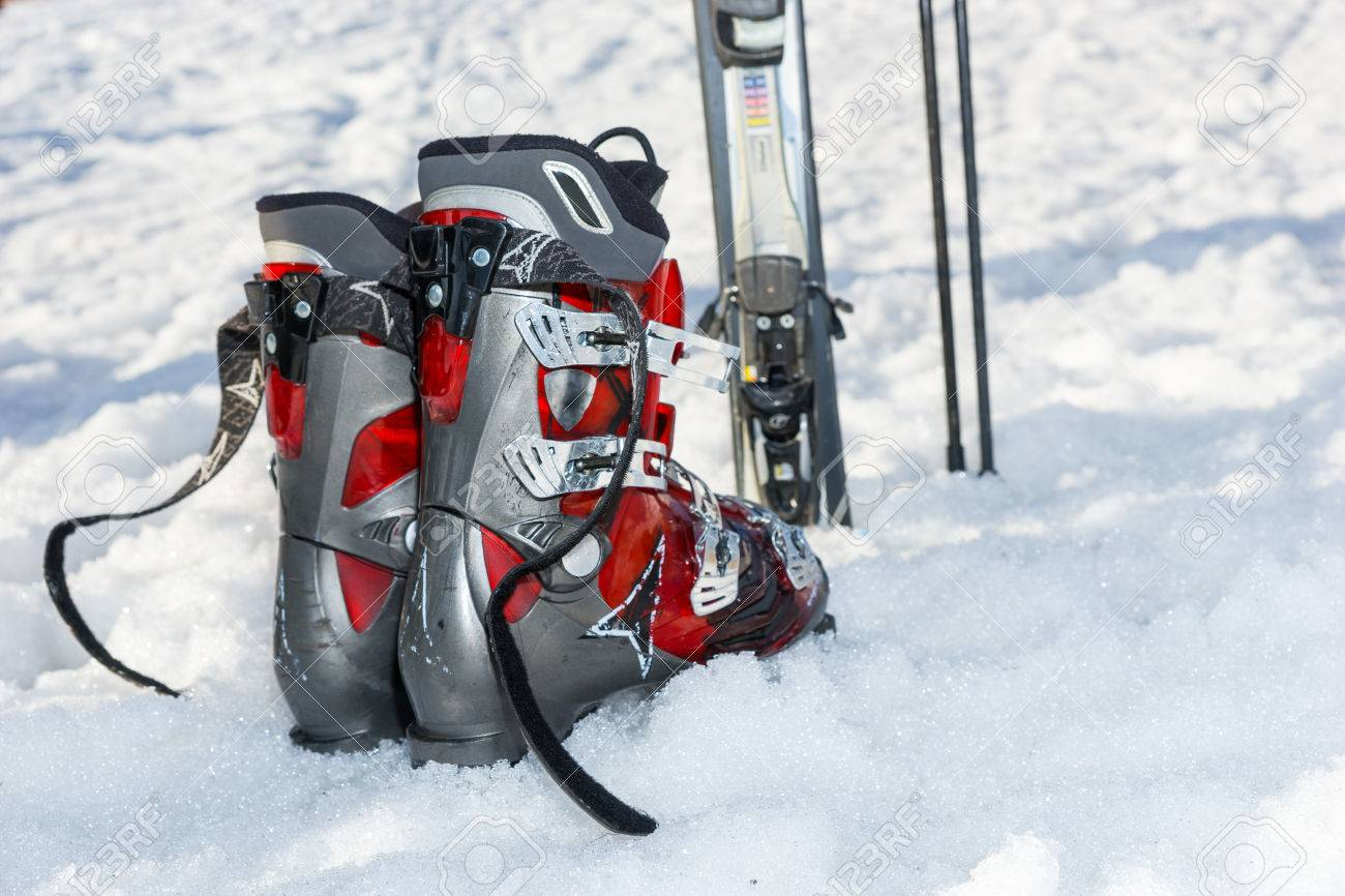 Close up of red and gray boots next to ski laying in fluffy snow in a ski-resort in winter period - 78175532