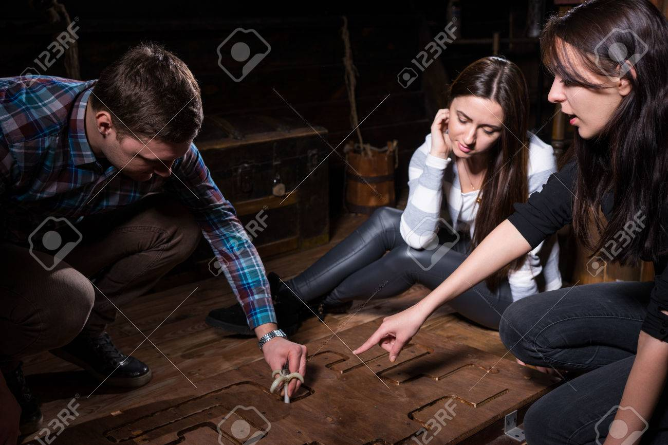 Young people trying to solve a conundrum to get out of the trap, escape the room game concept - 78209204