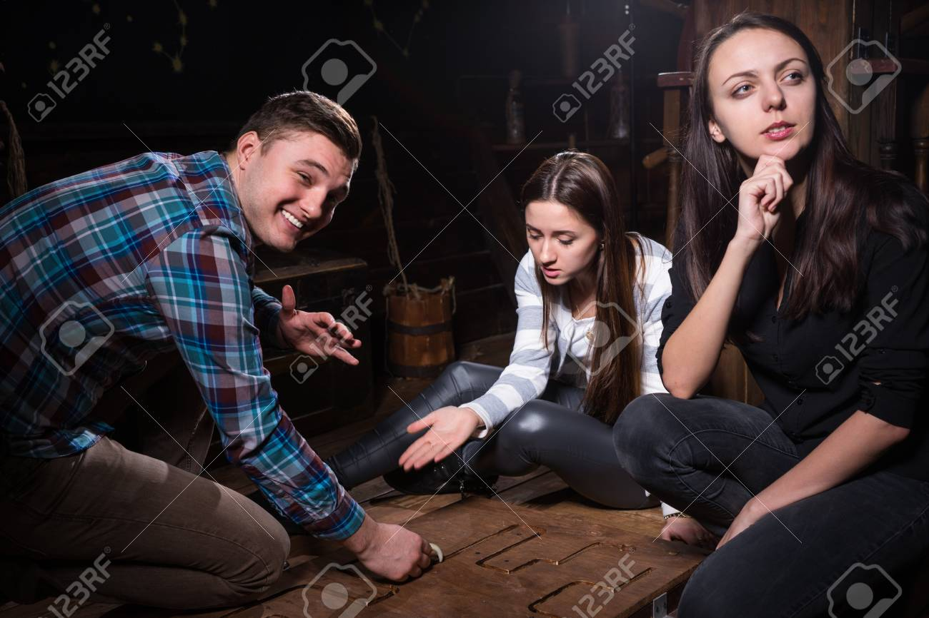 Young people thinking and moving parts of a conundrum to get out of the trap, escape the room game concept - 78232581
