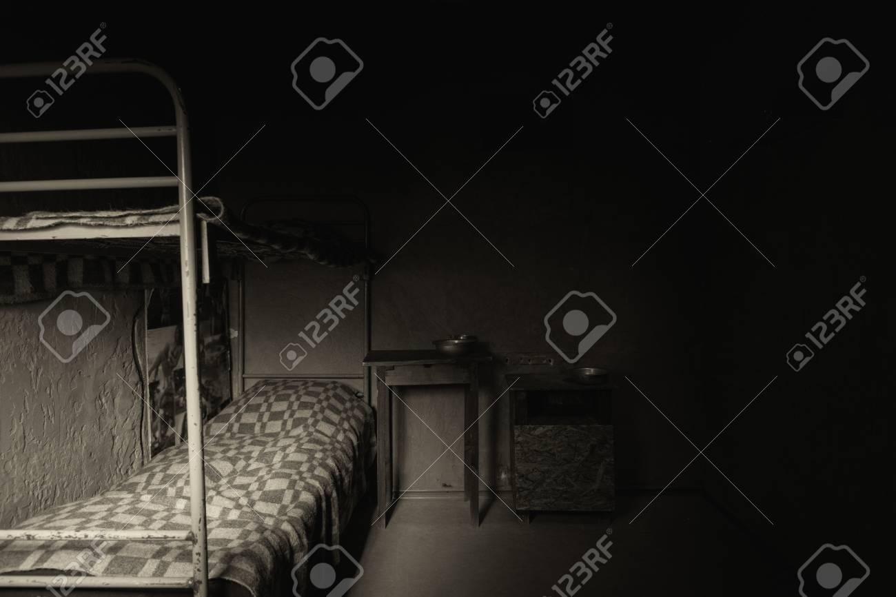 Image En Noir Et Blanc D Une Cellule De Prison Vide Sombre Avec Lit Superpose En Fer Et Table De Chevet Avec Plats En Aluminium