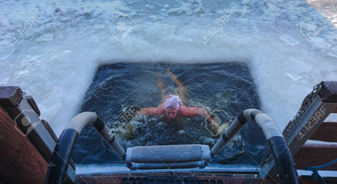 Person emerging from a swimming hole cut in the frozen ice surface of a lake viewed from the top of the exit steps - 103610720