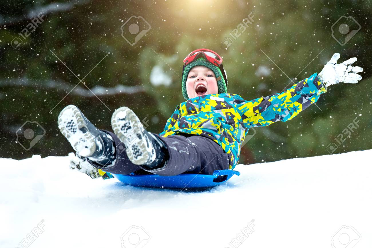 Christmas Vacation Sled.Boy Sledding In A Snowy Forest Outdoor Winter Fun For Christmas