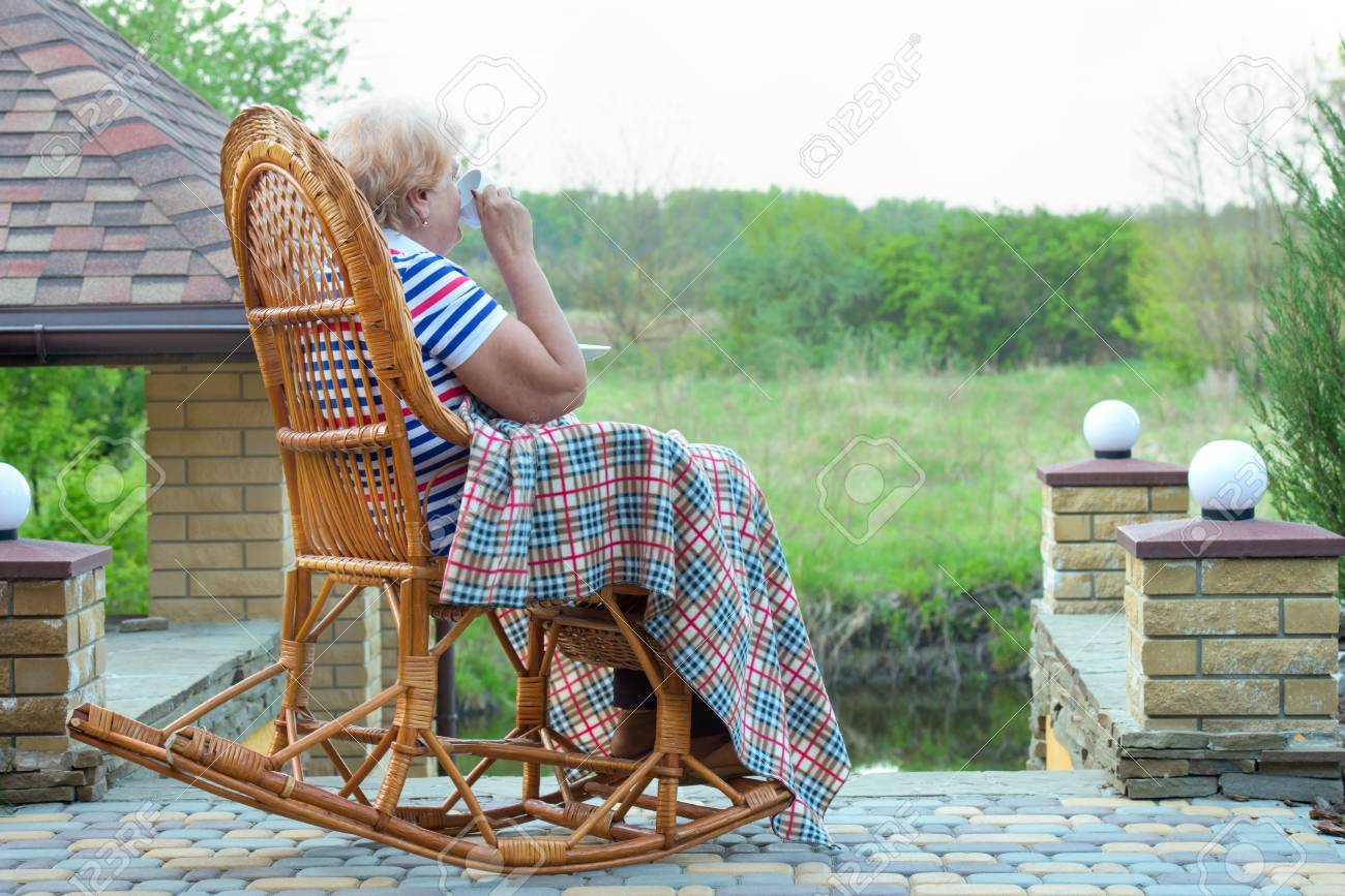 brand new 498ee 72057 An elderly woman sits in a wicker rocking chair and a cup of..